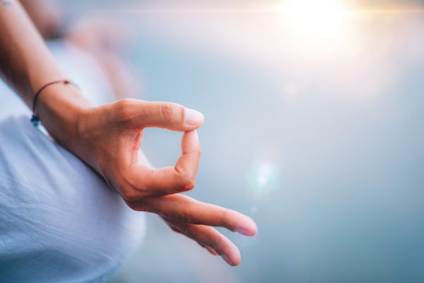Close up image of woman's hands in lotus position by the lake